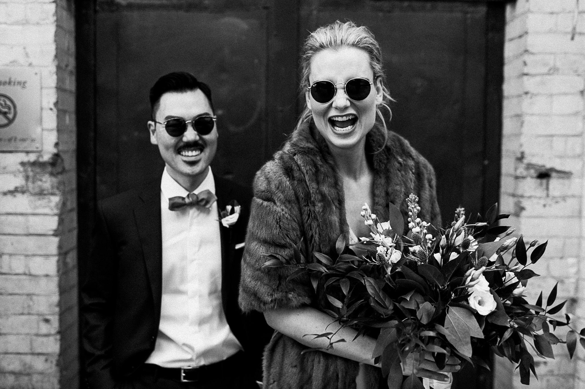 A black and white photo of a wedding couple that laughs wholeheartedly.