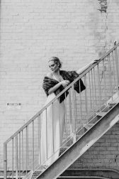 A black and white photo of a bride who stands on stairs in the backyard.