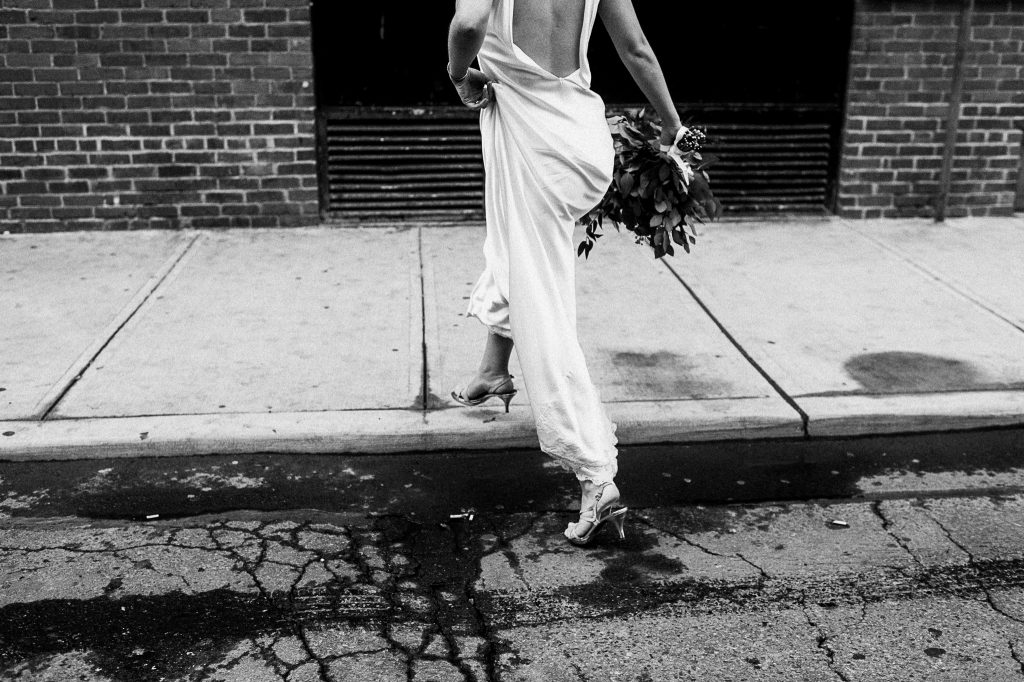 A black and white photo of a bride who makes a step from the street onto the sidewalk.
