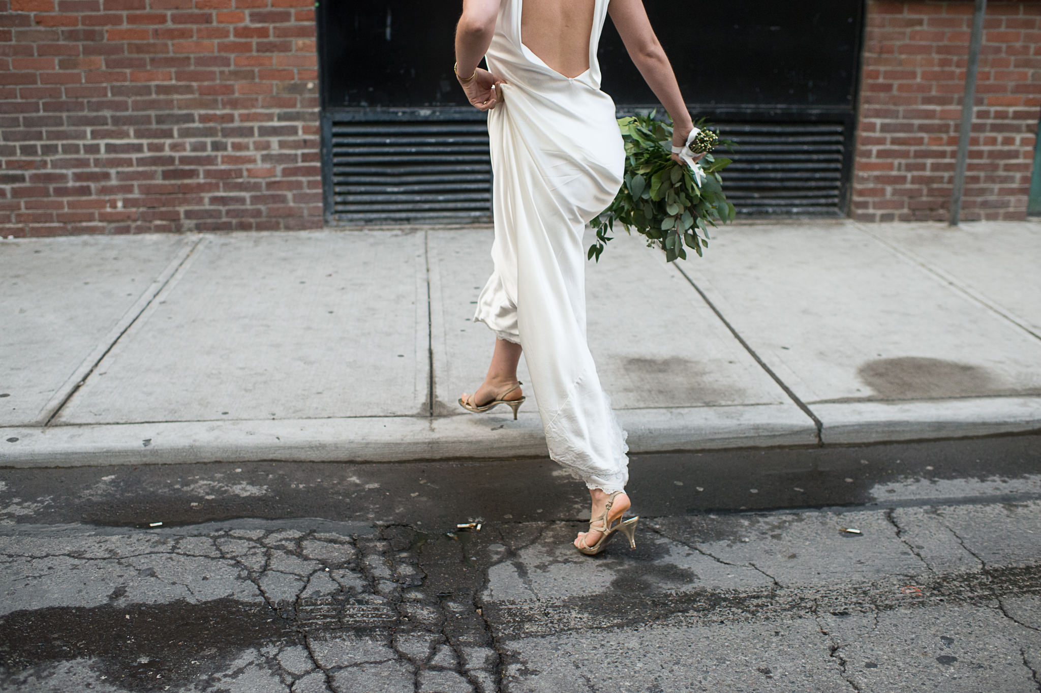 An unedited photo of a bride who makes a step from the street onto the sidewalk.