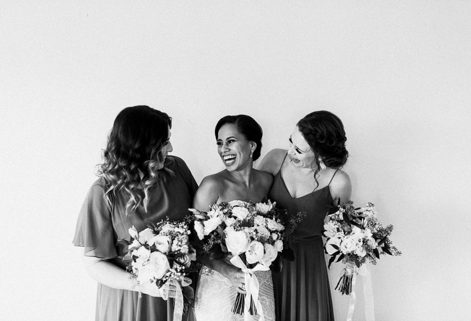 A black and white photo of a bride and her two bridesmaids.