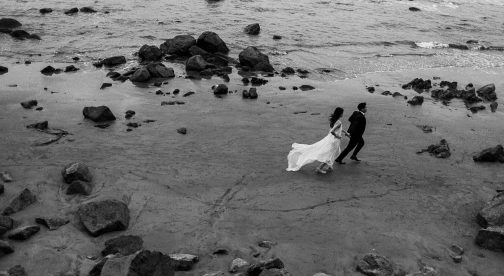 A black and white photo of a wedding couple that walks along the beach.