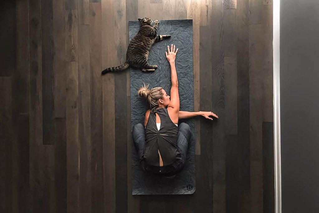 A woman is doing a yoga pose and her cat is lying next to her.