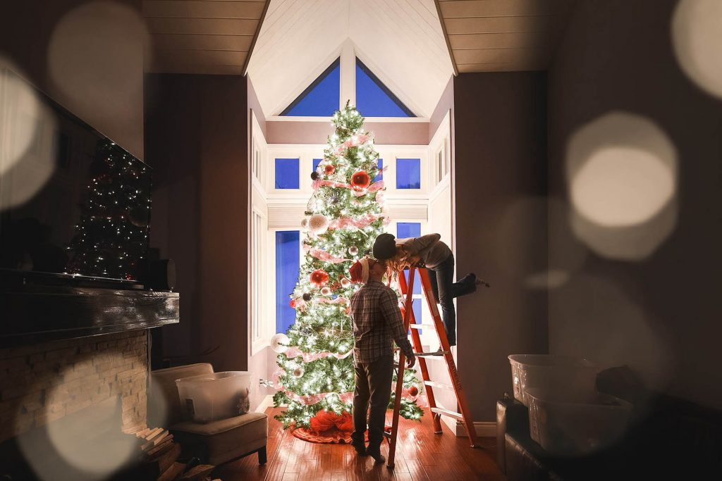 A couple is kissing each other whilst decorating their Christmas tree.