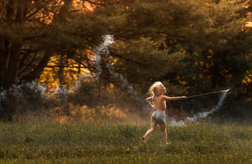 A child is holding a smoking stick and running through a meadow.