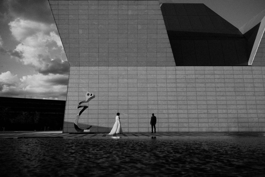 A black and white photo of a couple who stands in front of a modern building.