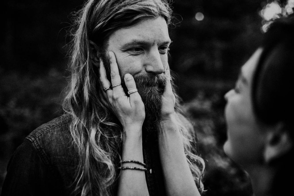 A black and white photo of a man whose face gets touched by his girlfriend.