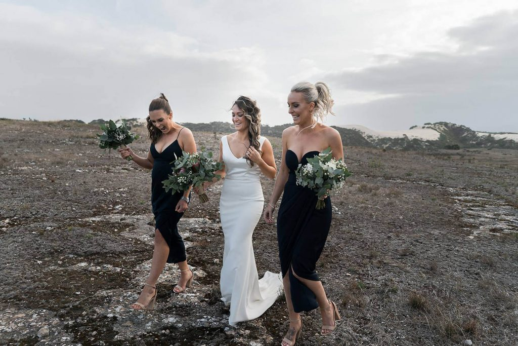 A bride and her two bridesmaids are walking through a dry meadow near the mountains.