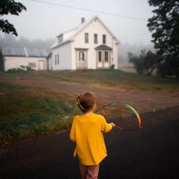 A child is walking on a road, towards a White white house.