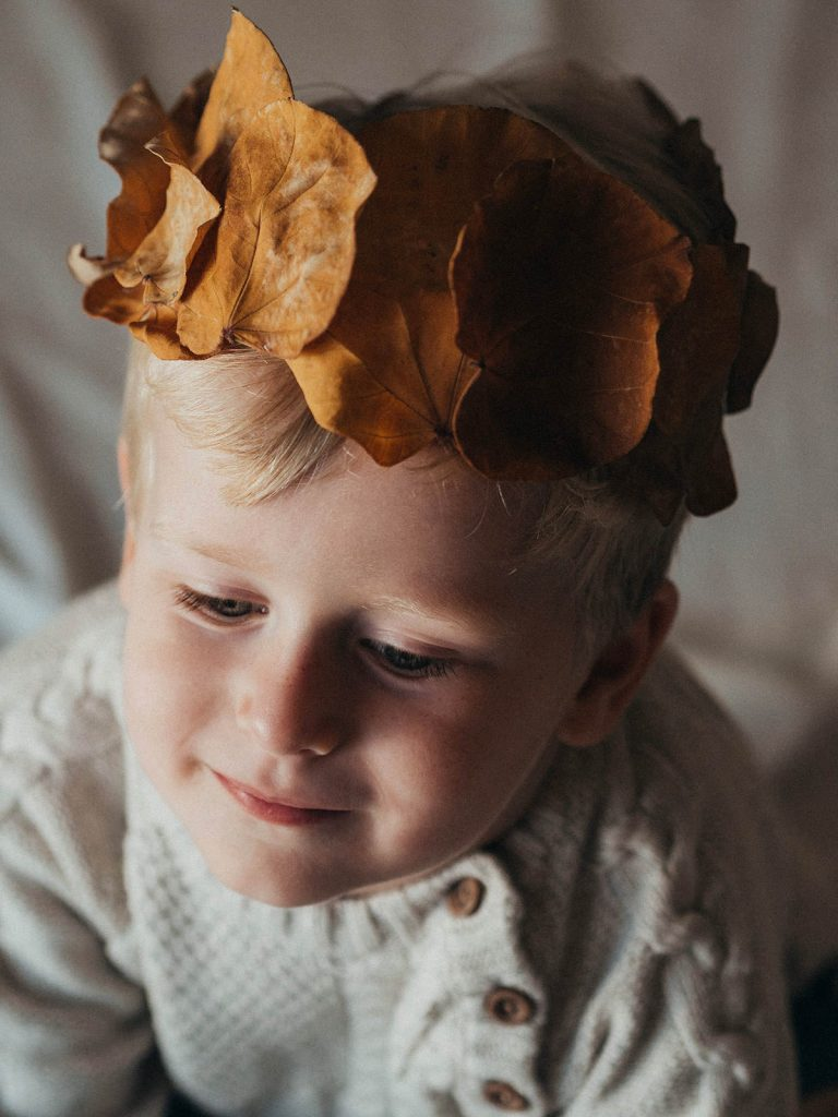 A headshot of a child wearing a crown made out of leaves.