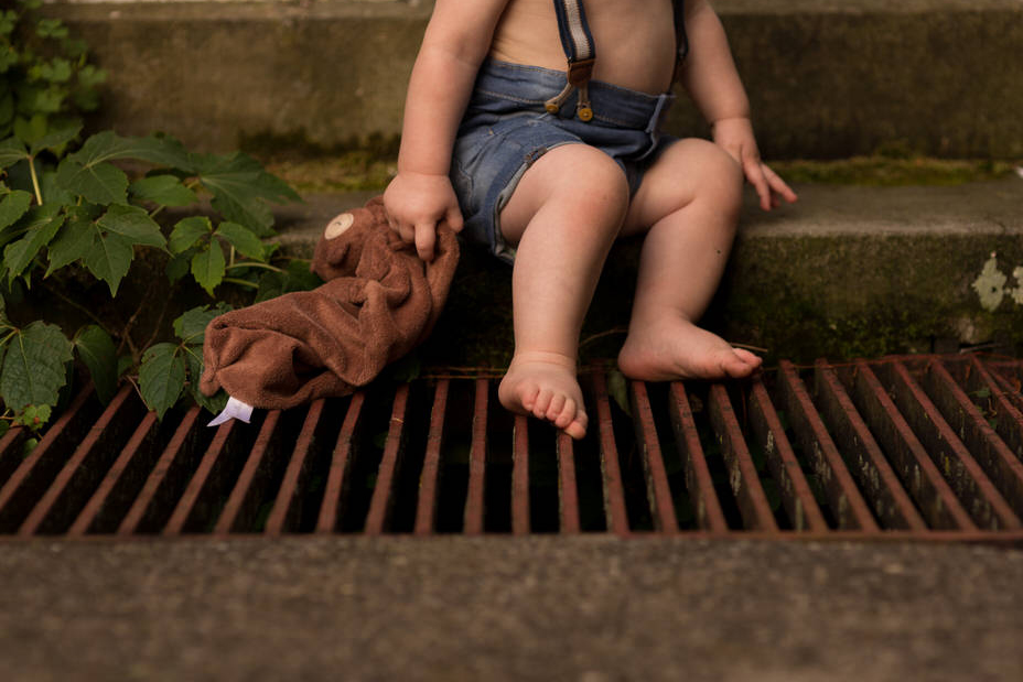 A child is sitting on stairs and holding a stuffed animal.