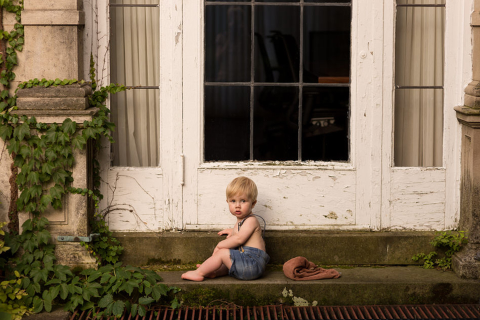 A child is sitting on stairs in front of a white door.