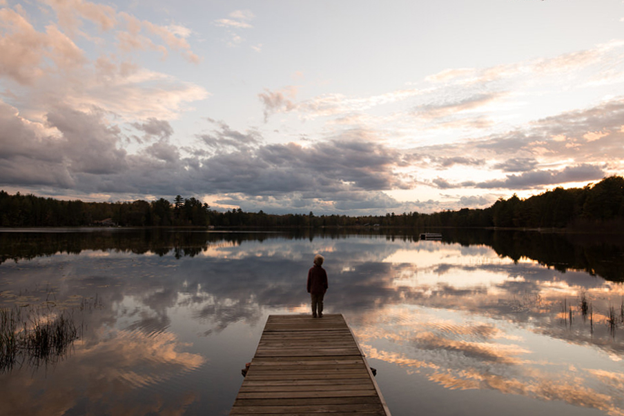 A child is standing at a lake.