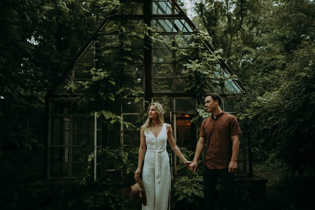 A couple stands in front of a greenhouse.