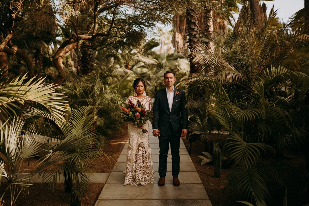 A wedding couple holds hands and is surrounded by tropical trees and flowers.