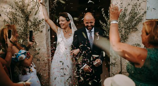 A wedding couple leaves the church, and the wedding guests throw confetti.