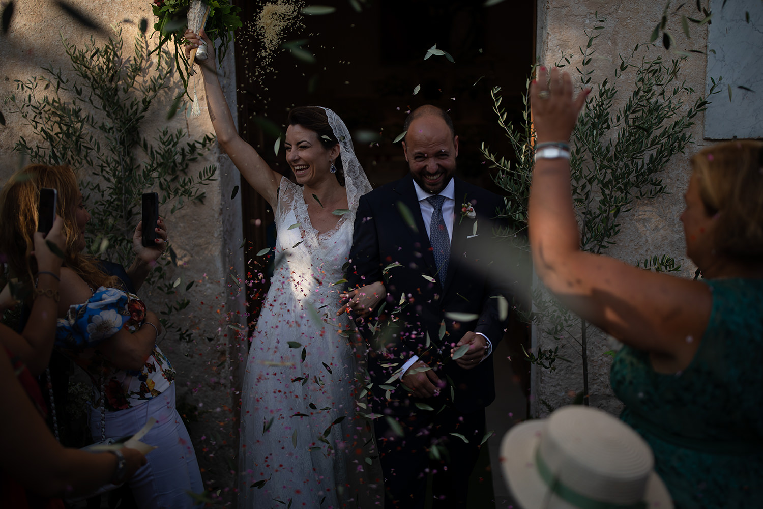 An unedited photo of a wedding couple that leaves the church, and the wedding guests throw confetti.