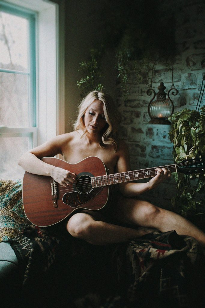 A naked woman plays guitar in her living room.