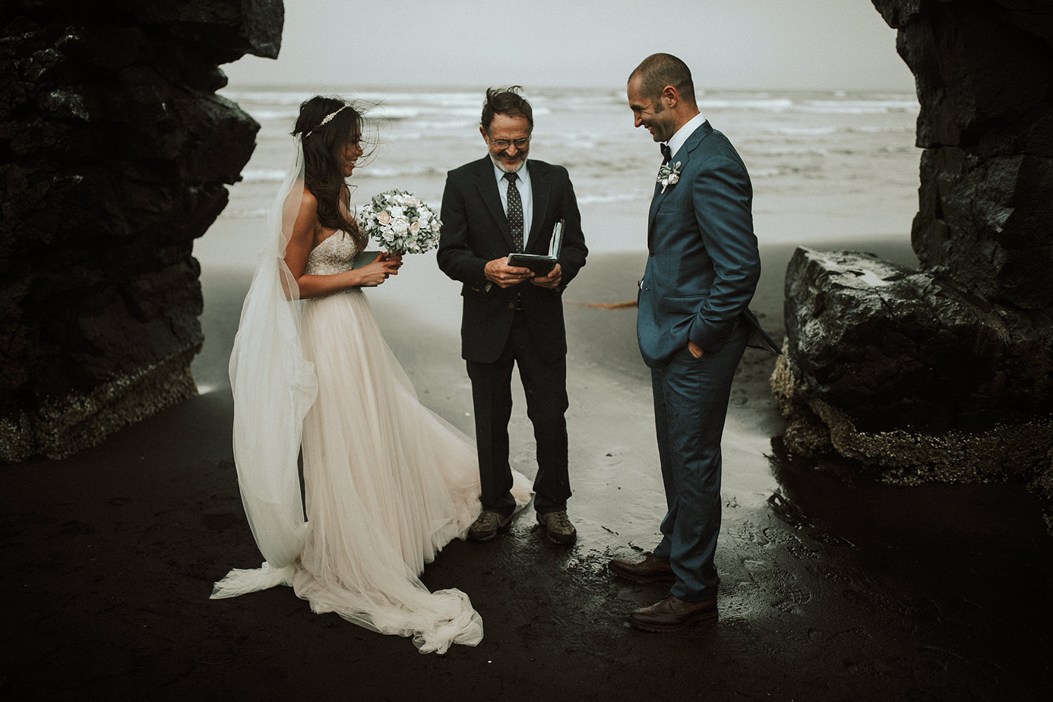 A wedding ceremony takes place at a beach.