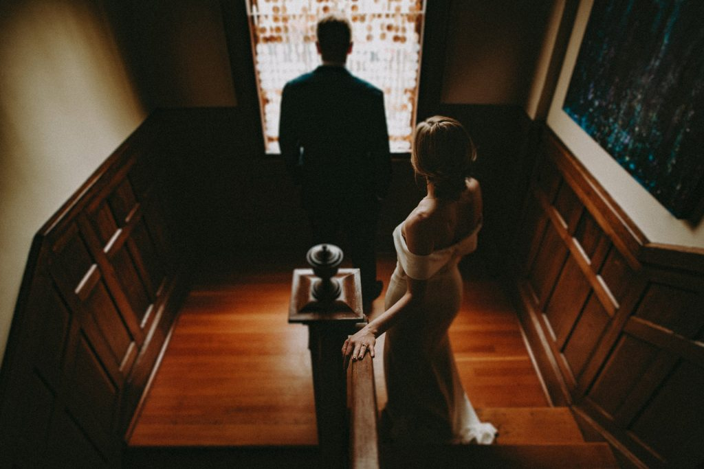 A groom looks outside the window while the bride walks down the stairs.