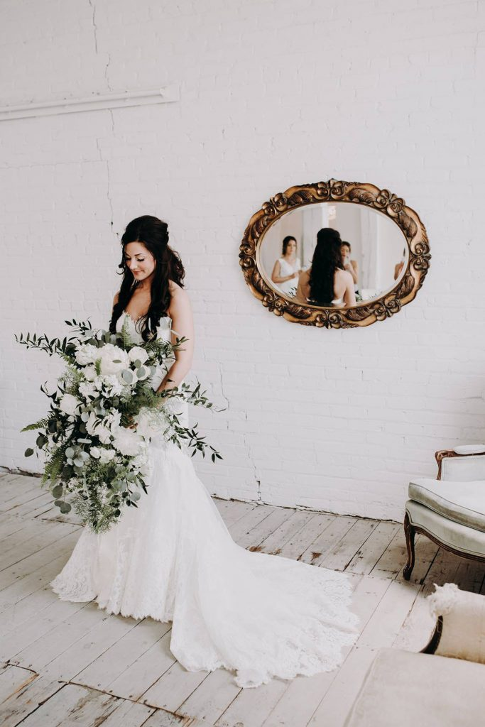 A portrait of a bride with her gigantic flower bouquet.