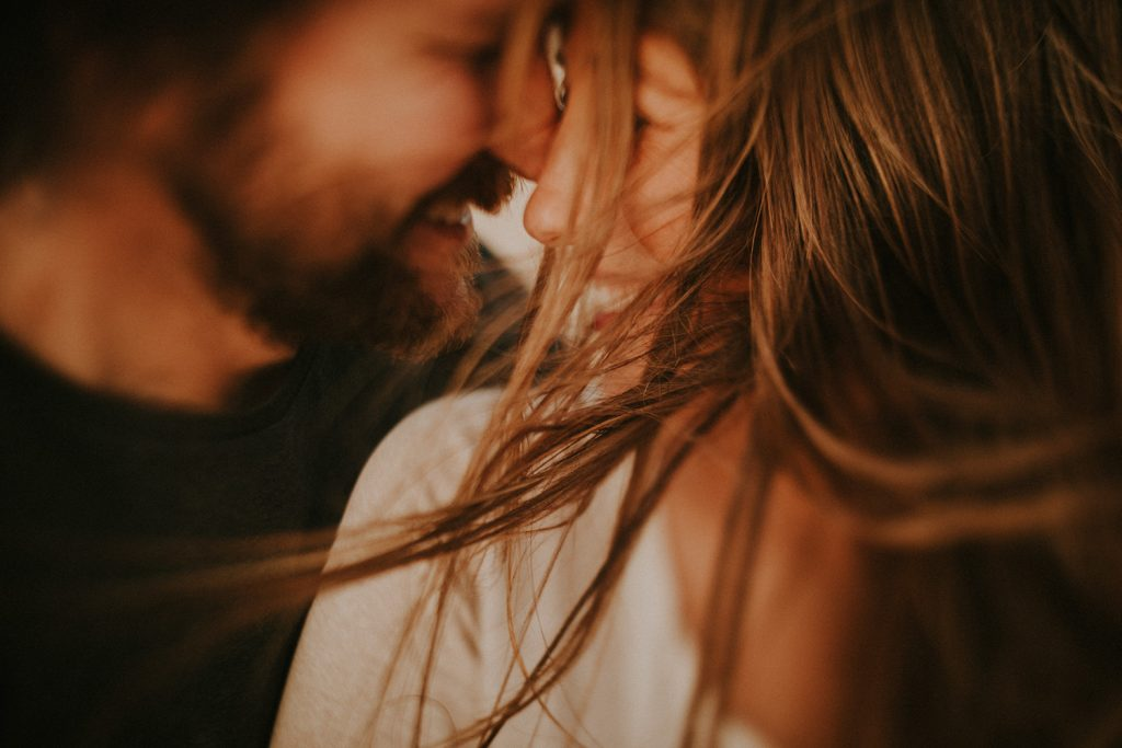 An artistic close-up photo of a couple on a windy day.
