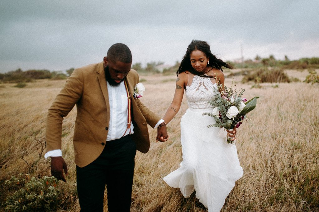 A wedding couple holds hands and walks through a field.