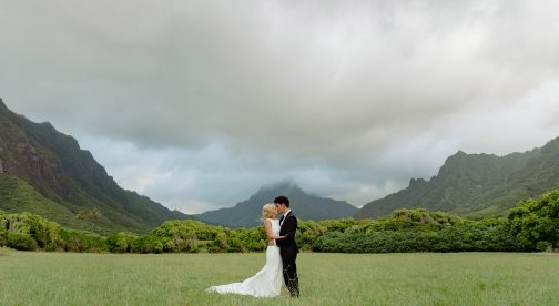 A wedding couple standing in a grass field in front of a mountain landscape.