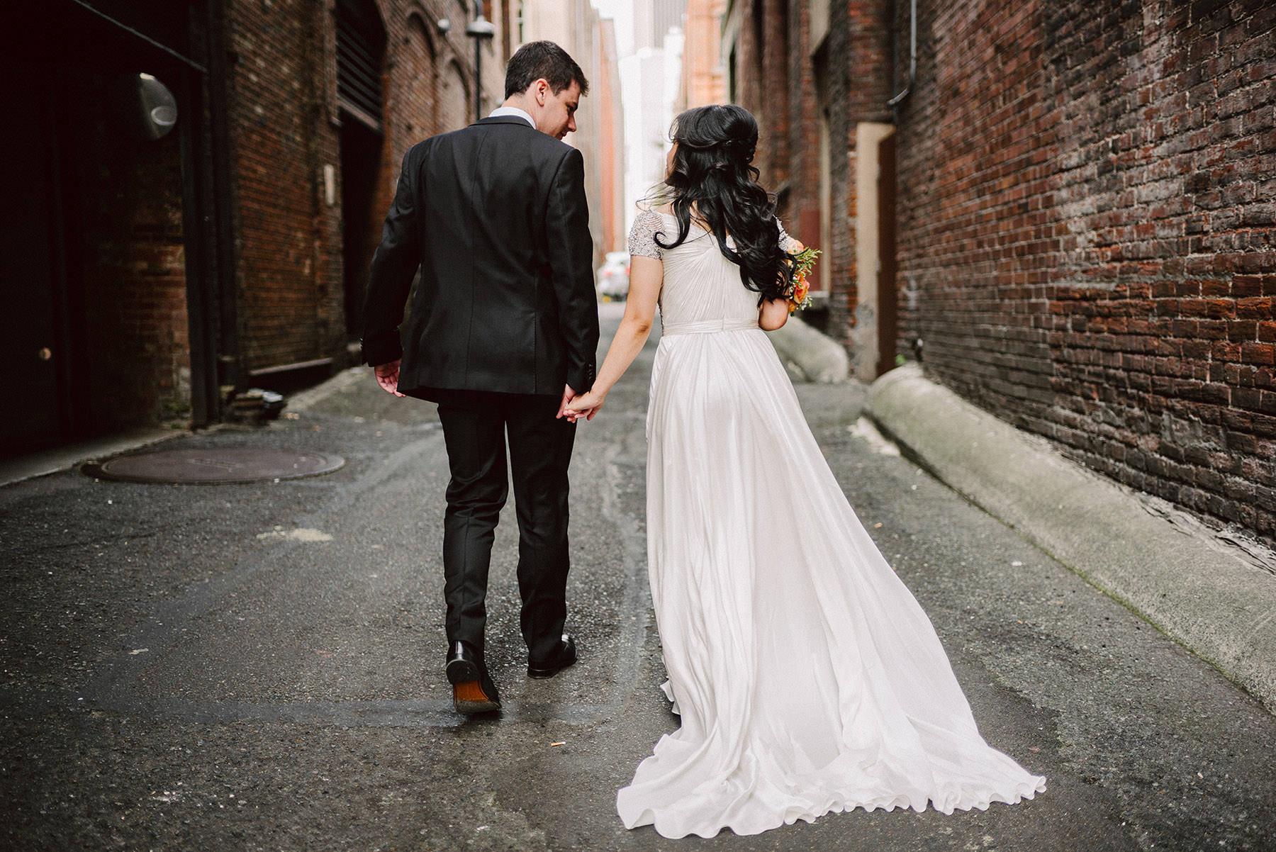 A wedding couple holds hands a walks through a backyard alley.