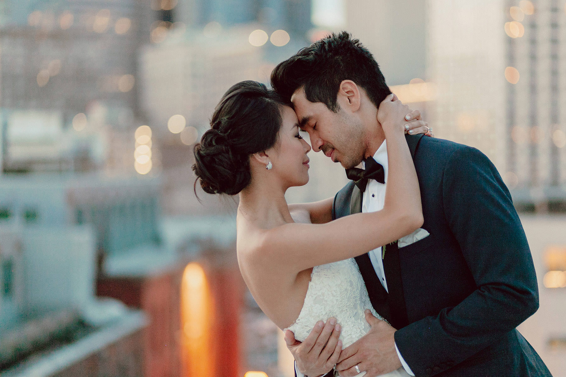 A wedding couple that stands on a rooftop and holds each other closely.