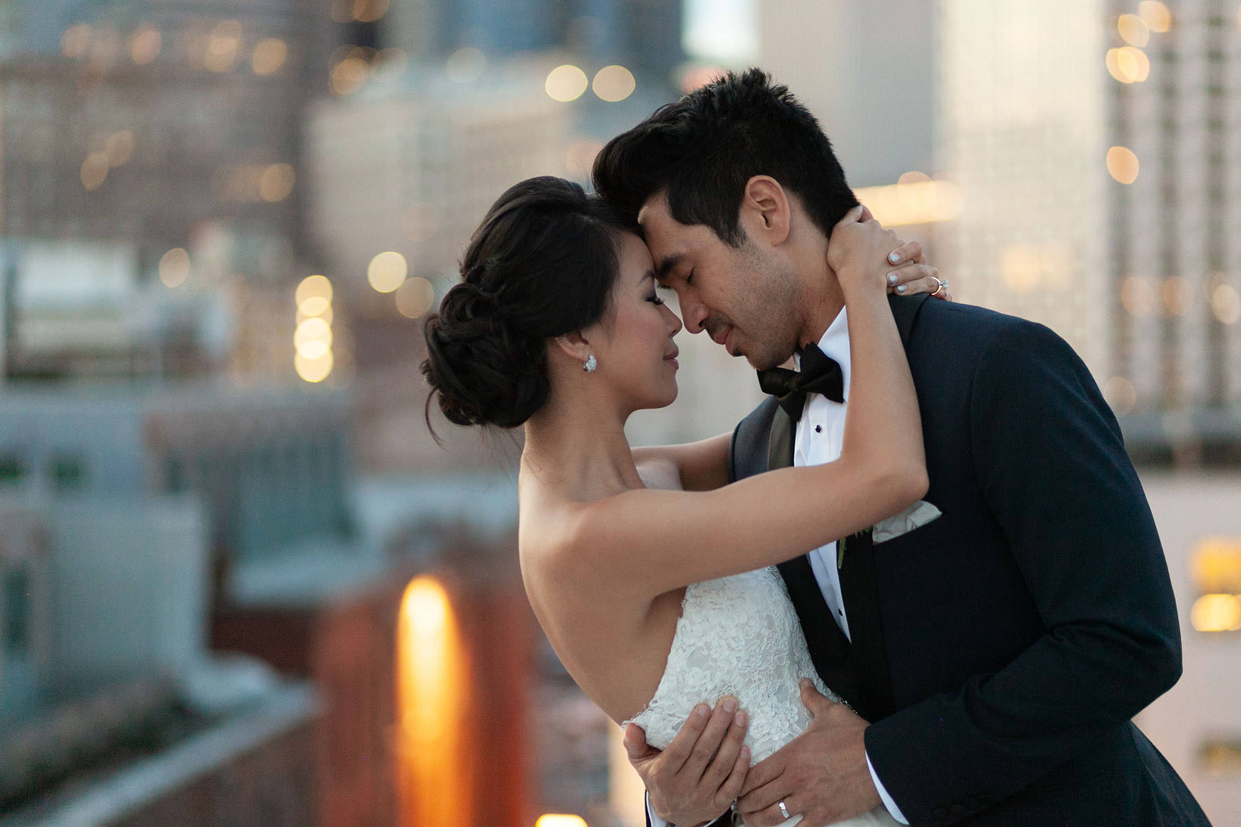 An unedited photo of a wedding couple that stands on a rooftop and holds each other closely.