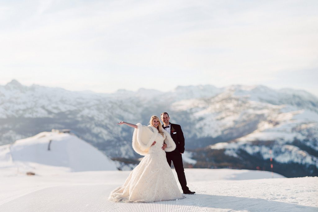 A wedding couple stands on a ski slope on top of a mountain.