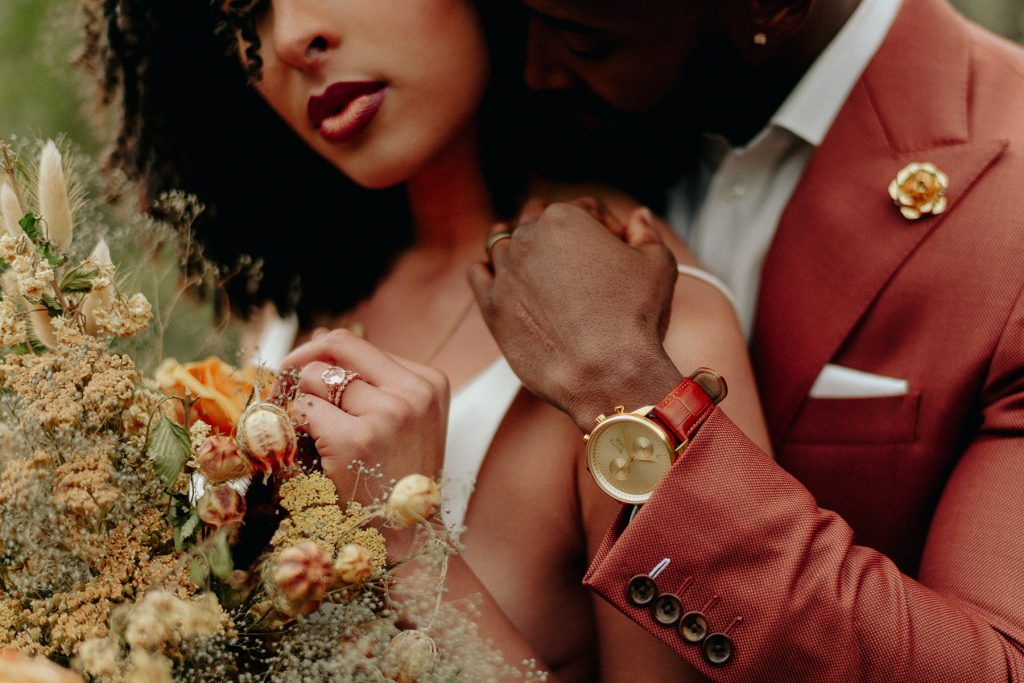 The bride & groom embrace each other closely, and you can take a closer look at her flower bouquet and his golden watch.