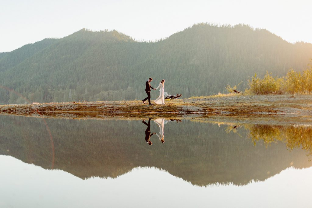 A wedding couple walks along a lake, and there's a reflection of the whole scenery in the lake.