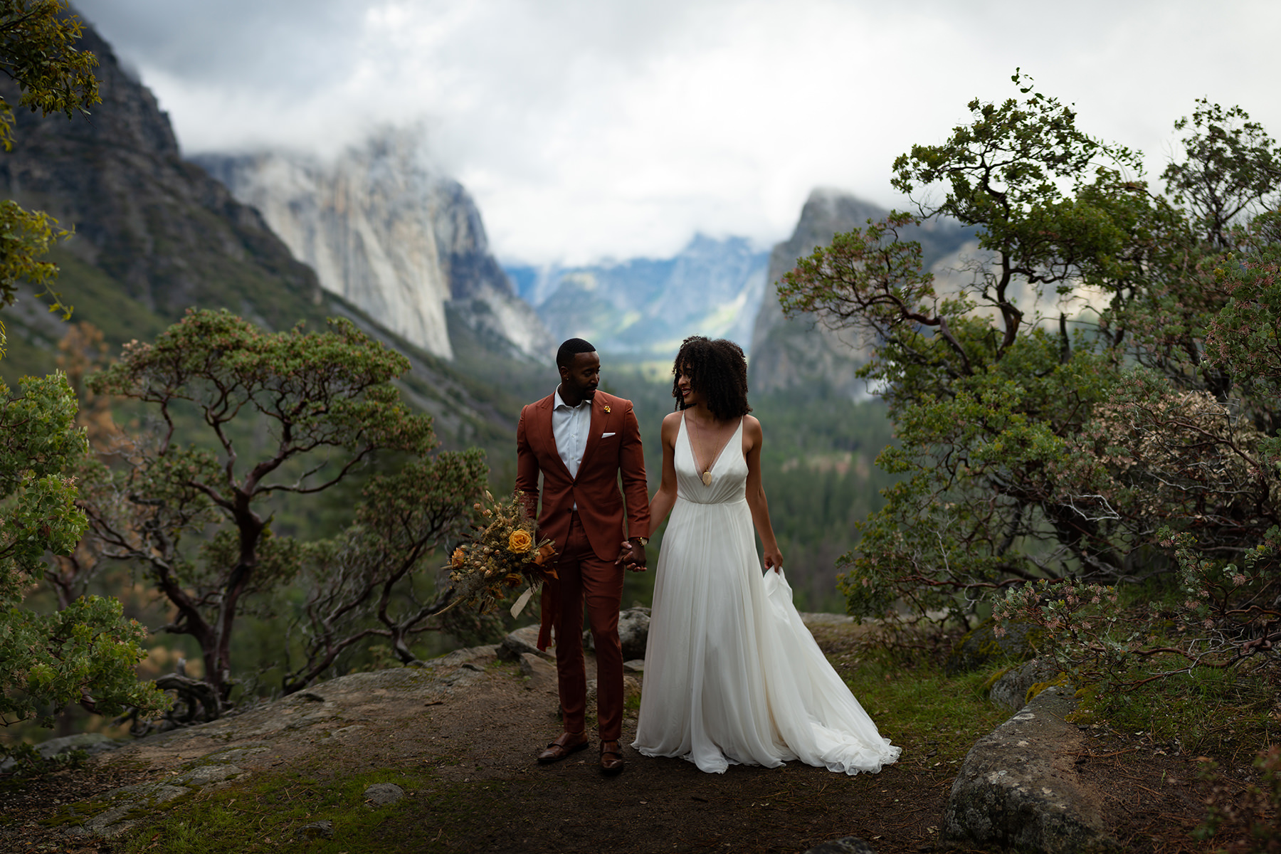 An unedited image of a wedding couple stands on a cliff in a National Park surrounded by trees and mountains.