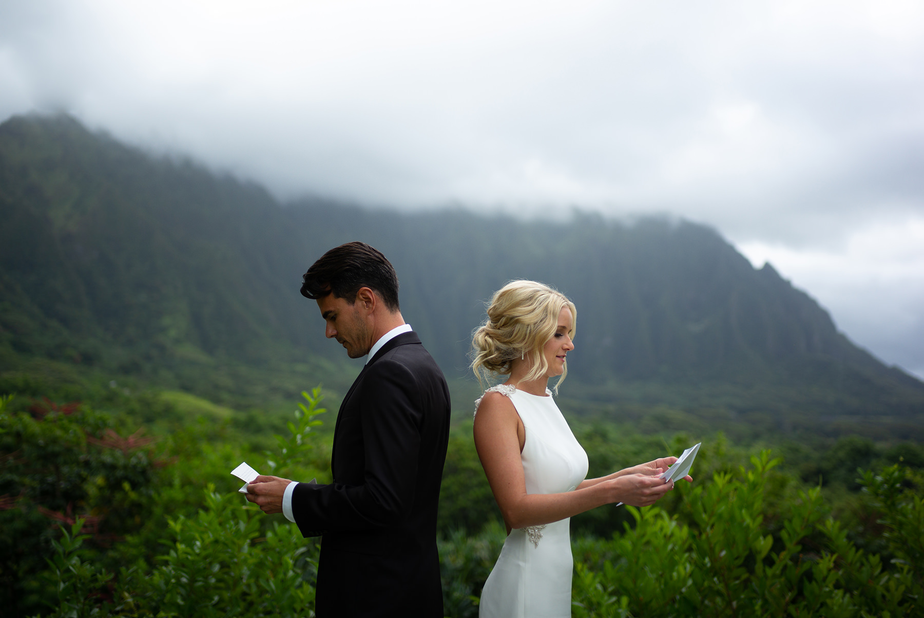 An unedited photo of the bride and groom stand back to back and read their vows.