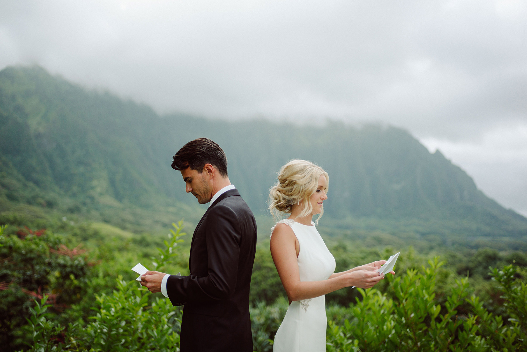 A photo of the bride and groom stand back to back and read their vows edited with the wedding presets.