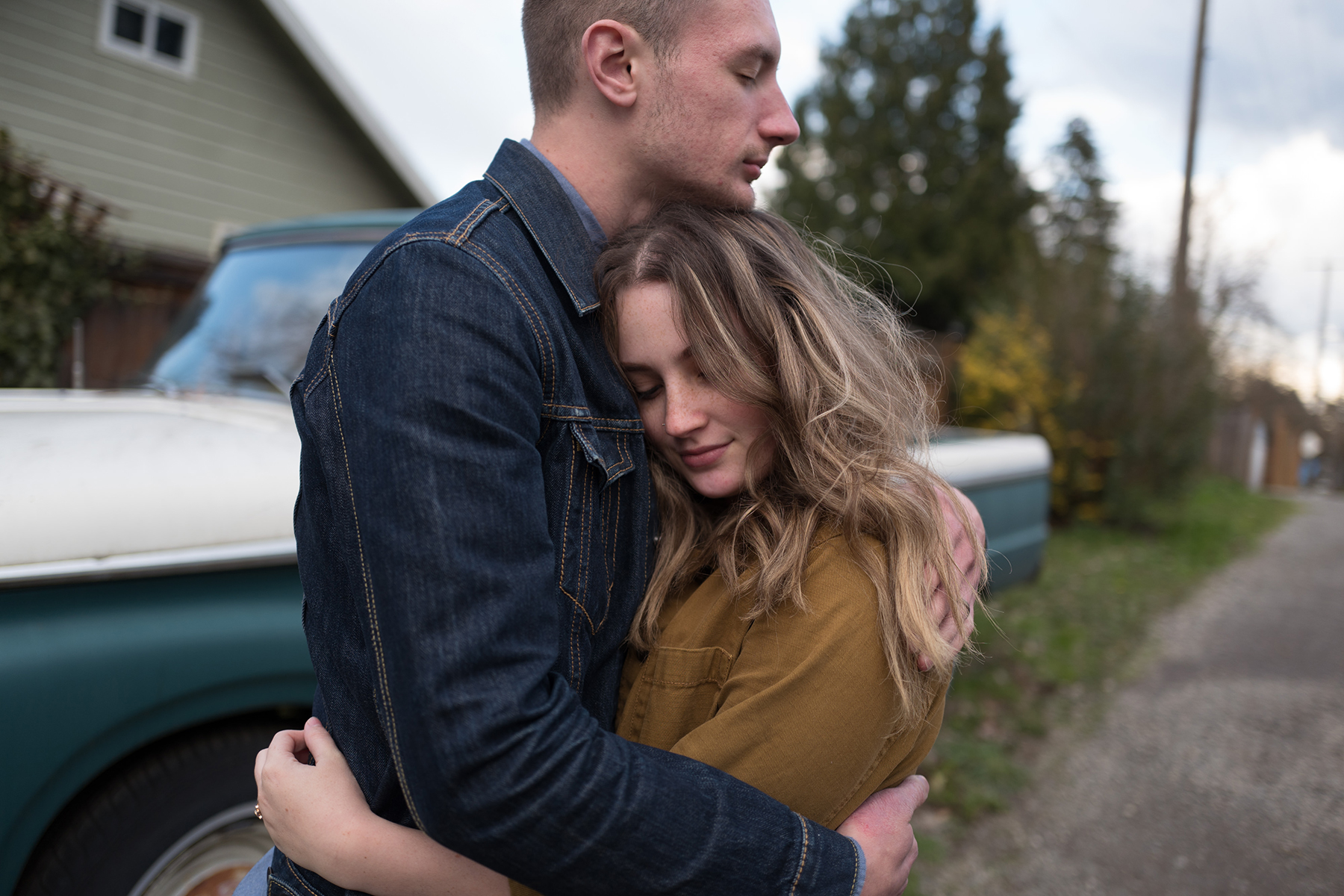 An unedited photo of a couple that embraces each other closely in front of a car.