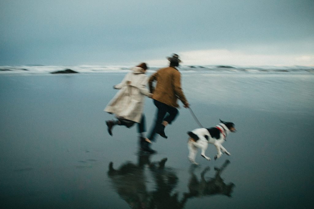 A blurry photo of a couple and a dog running at the beach.