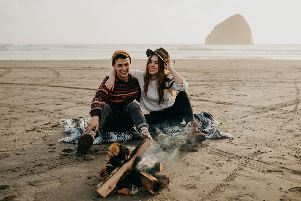 A couple sits at a bonfire at a beach in Oregon.