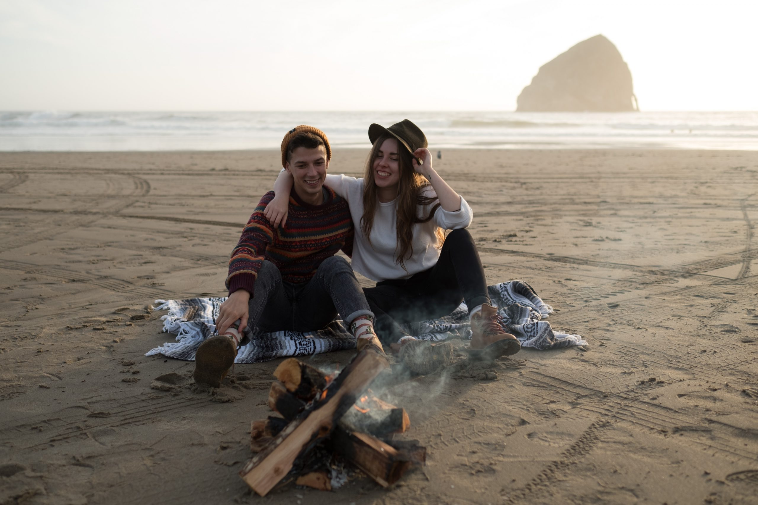 An unedited photo of a couple that sits at a bonfire at a beach in Oregon.