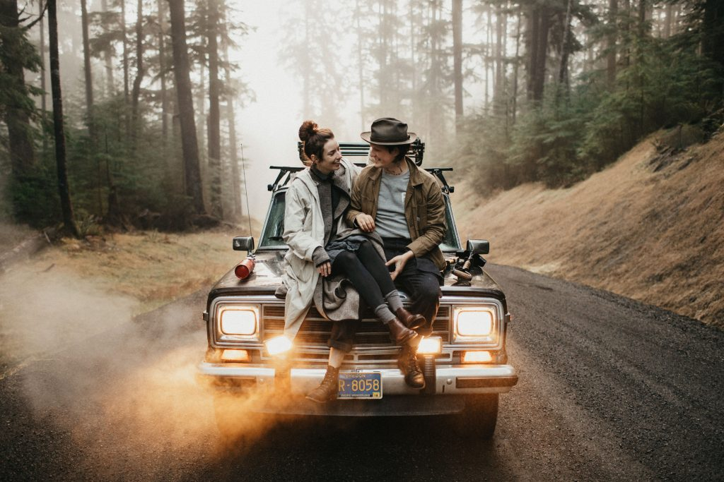 A couple sits on the bonnet of a car in the middle of a forest.
