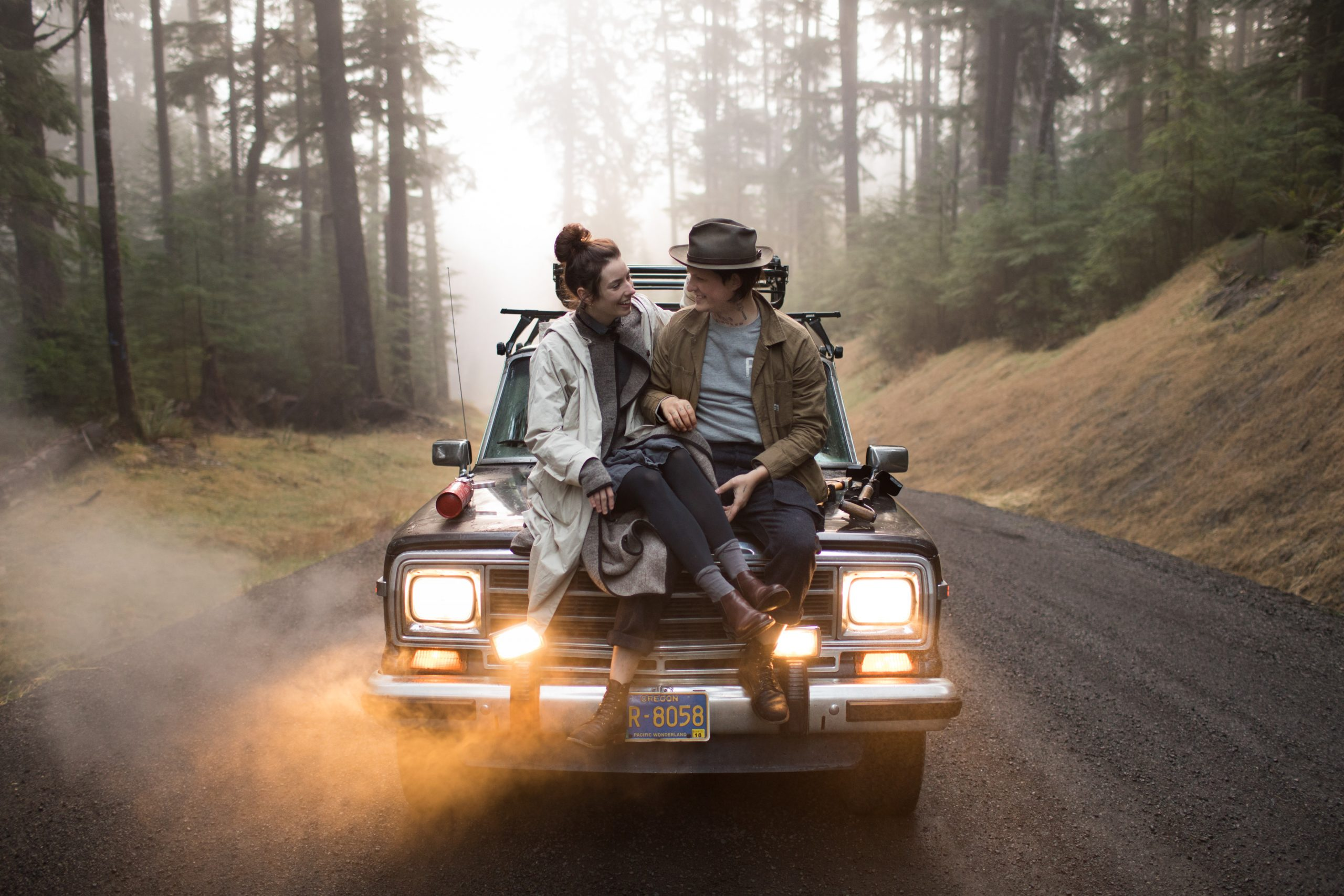 An unedited photo of a couple that sits on the bonnet of a car in the middle of a forest.