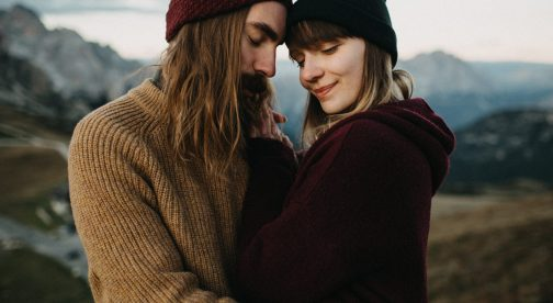 A man and a woman stand close together and have their eyes closed.