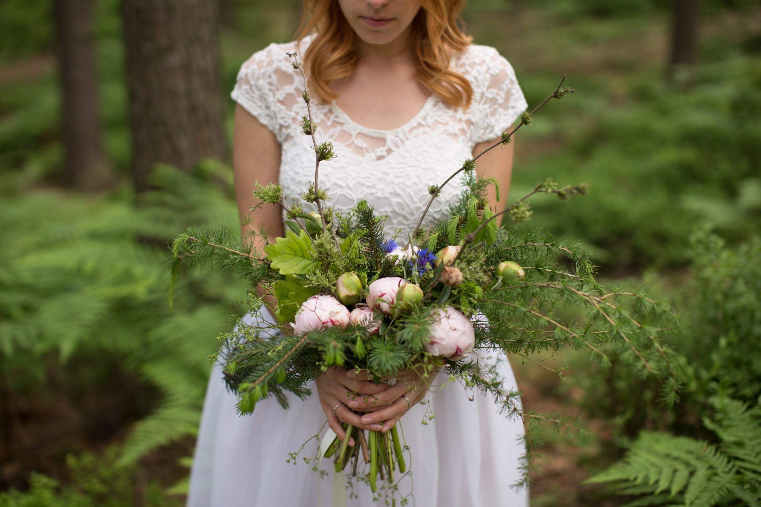 An unedited photo of a bride that is holding her bridal bouquet.