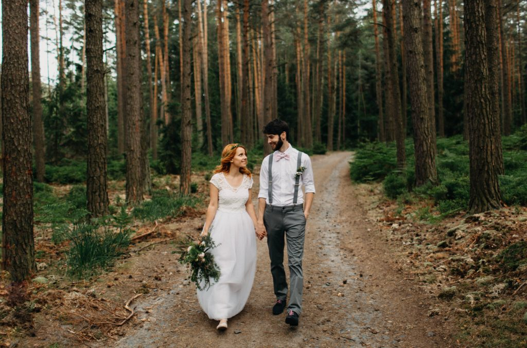 A wedding couple walks along a path in the forest.