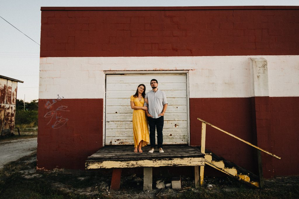 A couple that stands in front of a red and white building.