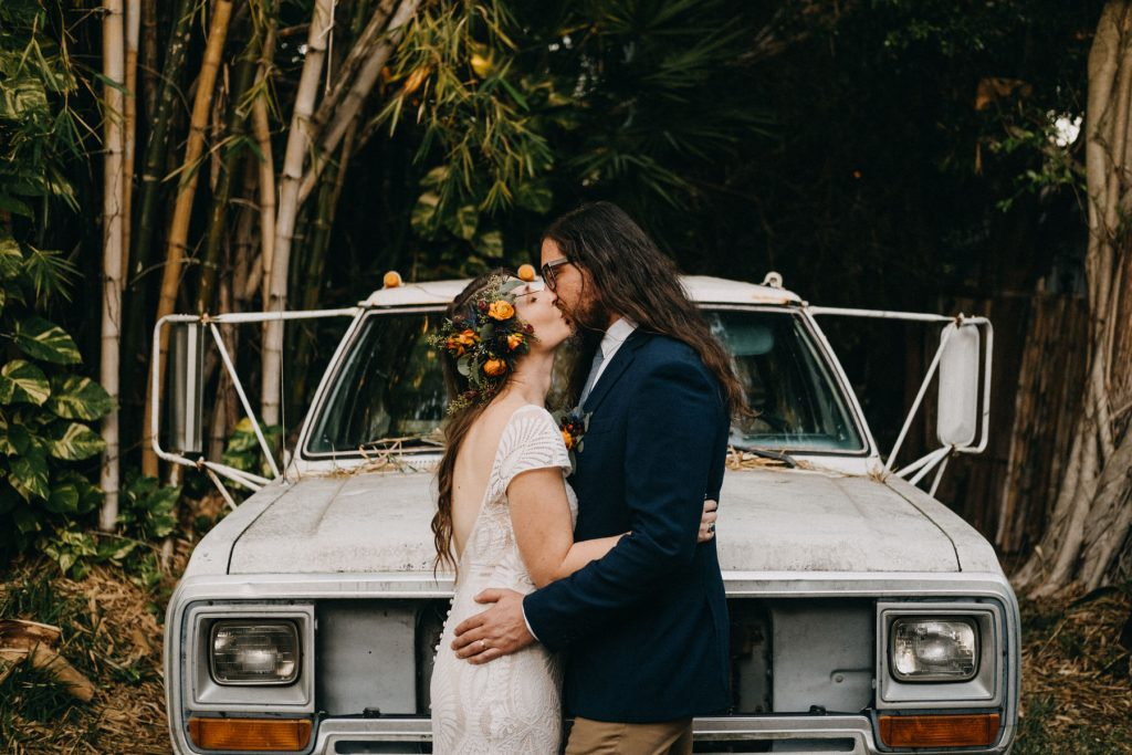a wedding couple kisses in front of their wedding car.