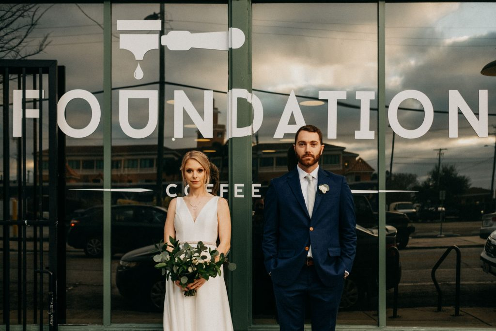 a wedding couple stands in front of a coffee bar.