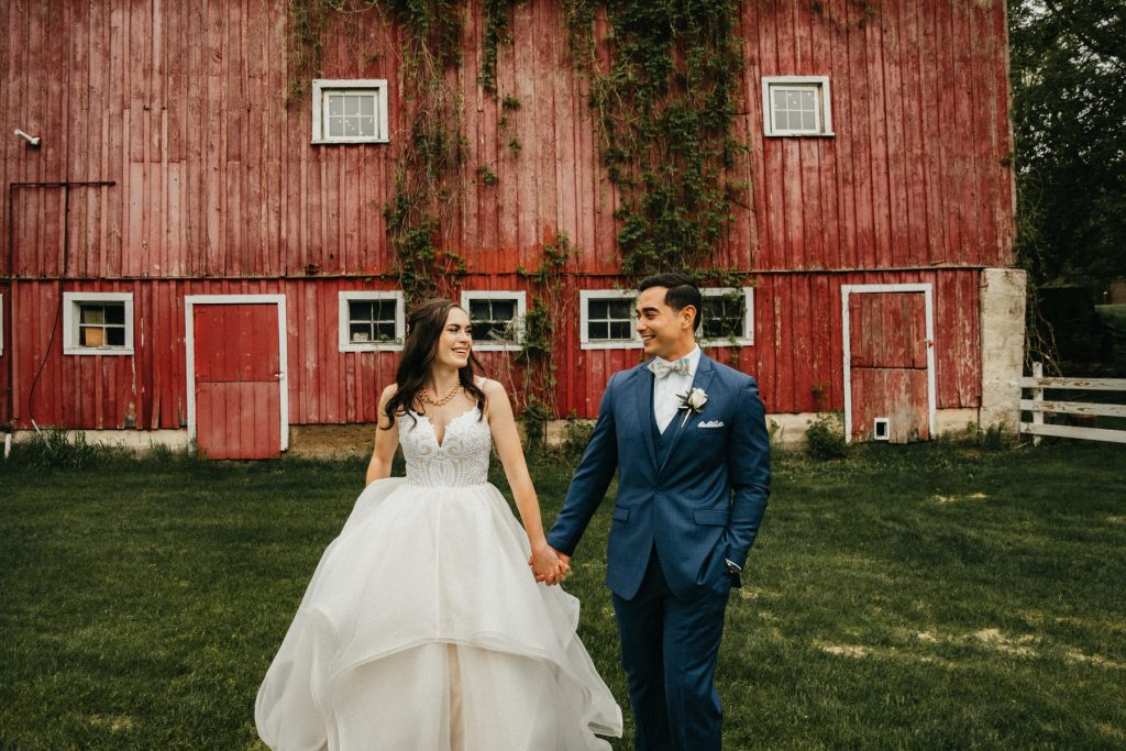 A wedding couple walks away from a red barn.